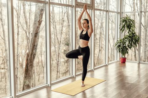 Faire du yoga dans son salon devant la fenêtre